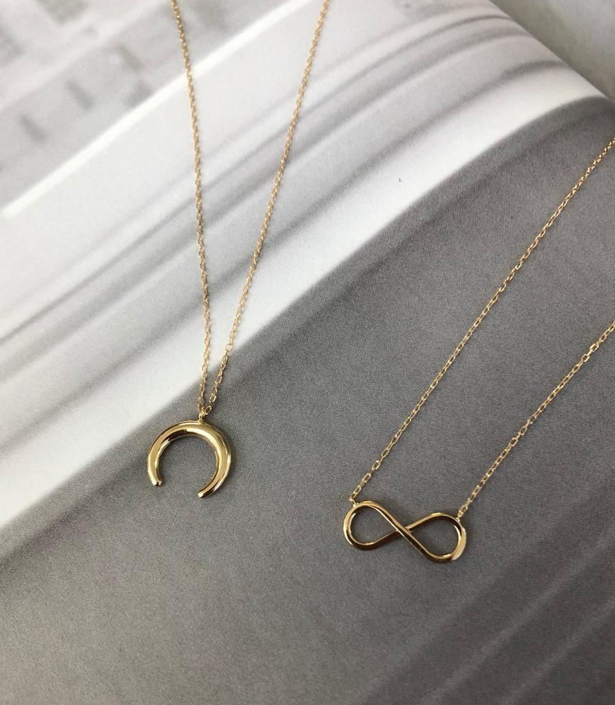 Cadenas con motivos en oro amarillo, uno de luna invertida (o cuerno)  y otro de infinito, ambos con cadena a 45 centímetros con anilla a 40 centímetros para poderlo hacer mas corto.