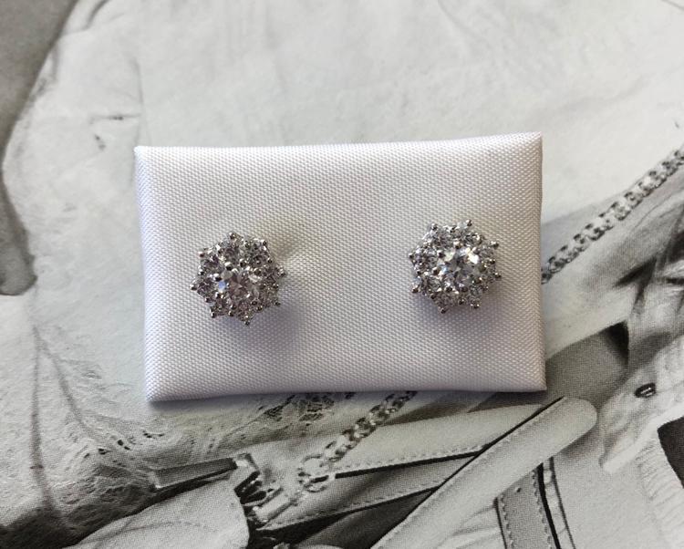 Pendientes de rosetón de 9 milímetros en oro blanco con 9 circonitas con garras cada uno y cierre de presión.