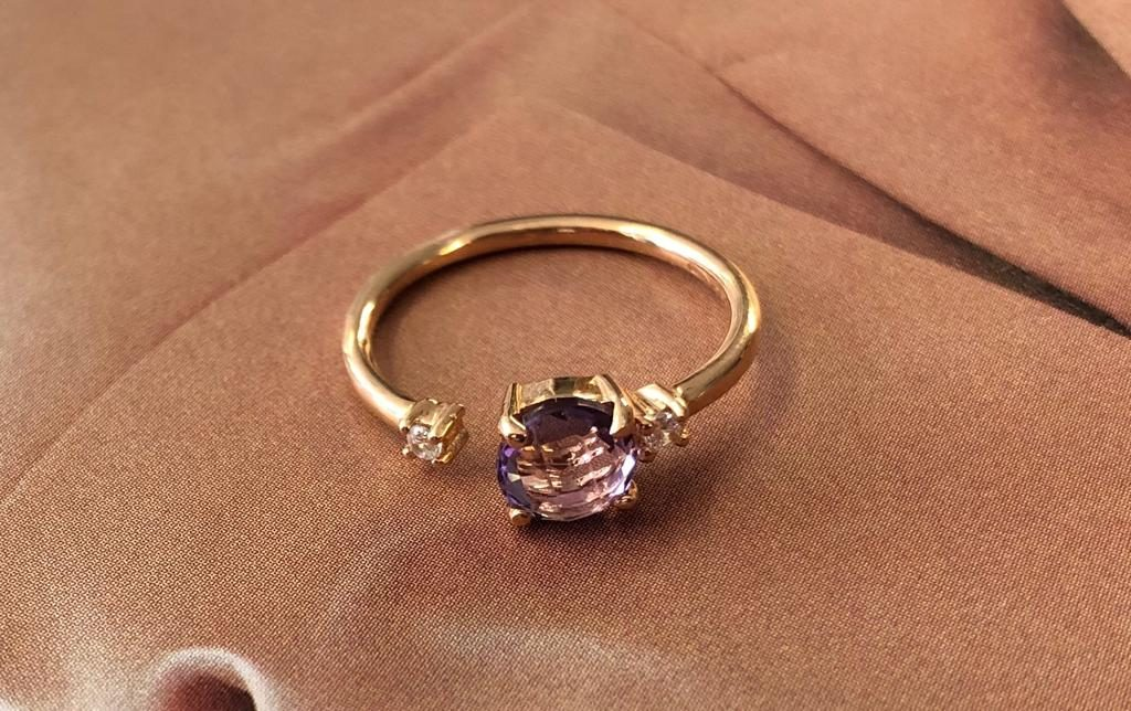 Ahora que se acerca el buen tiempo (y siempre) apetece lucir joyas favorecedoras y coloridas y que más buena opción que una sortija de oro rosado con una amatista tallada de seis milímetros engastada en 4 garras y dos circonitas, una a cada lado, también engastadas con 4 garras.