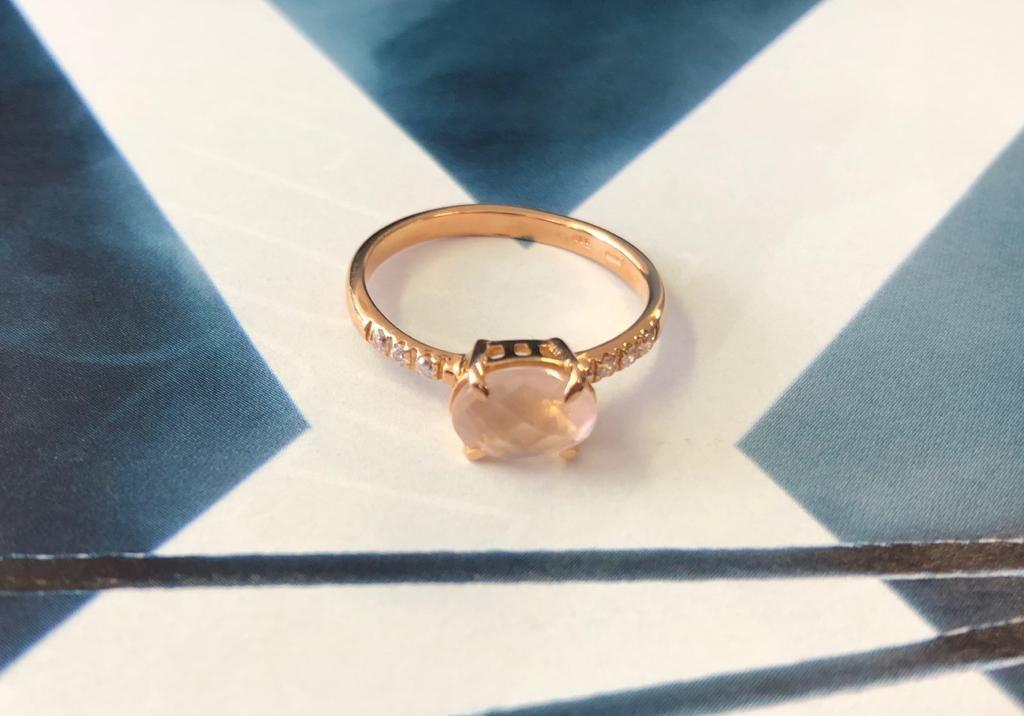 Anillo de oro rosado con una piedra de oro rosa de 6 x 8 milímetros engastada en cuatro garras y con tres circonitas a cada lado.