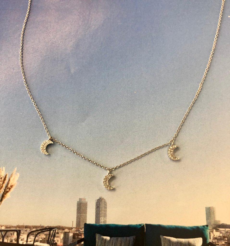 Cadena forzada a 42 centímetros con tres colgantes en forma de lunas, cuajadas de brillantes ( 33 brillantes que en total hacen 0,06 quilates), en oro blanco.