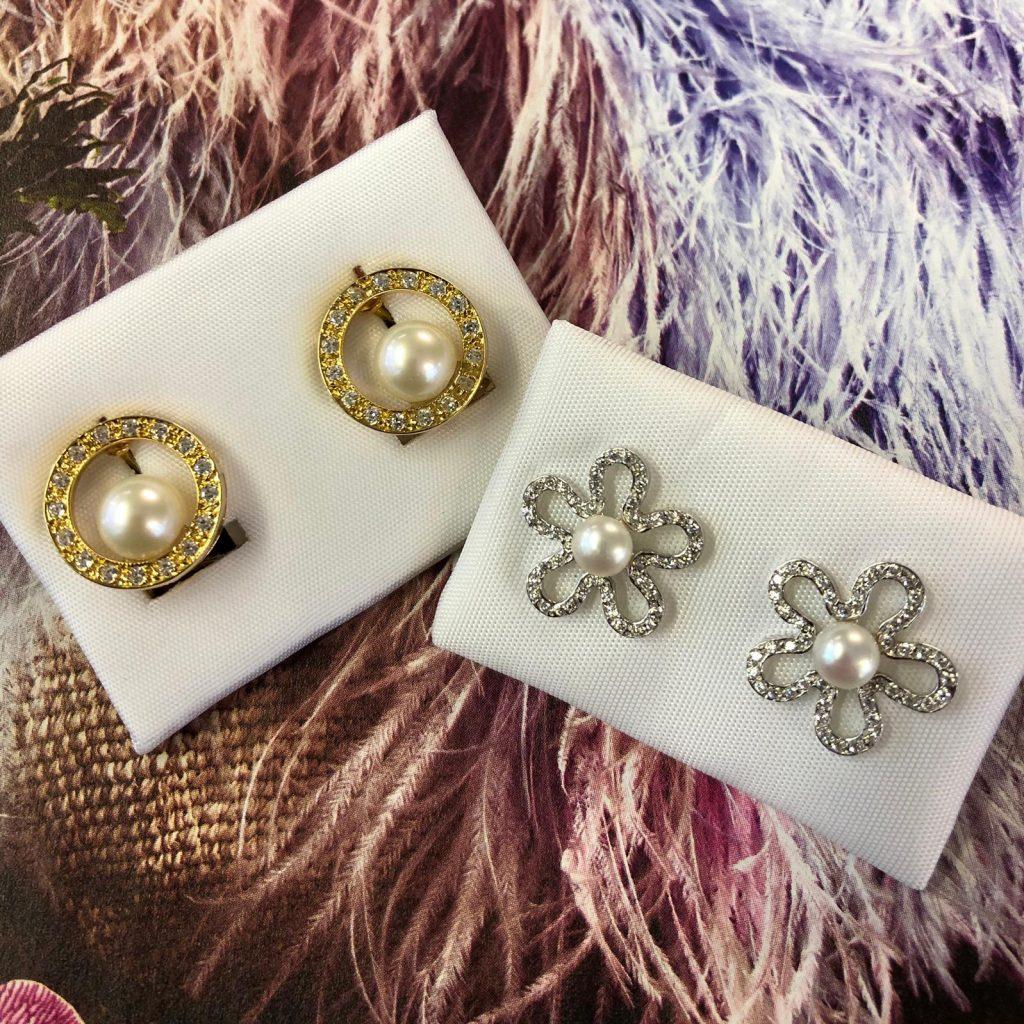 Pendientes con perlas, unos en oro amarillo con perlas de 7 milímetros y 16 circonitas cuajadas en circulo con cierre omega, otros de oro blanco en forma de flor cuajado de circonitas con perlas de 5 milímetros y cierre de presión.