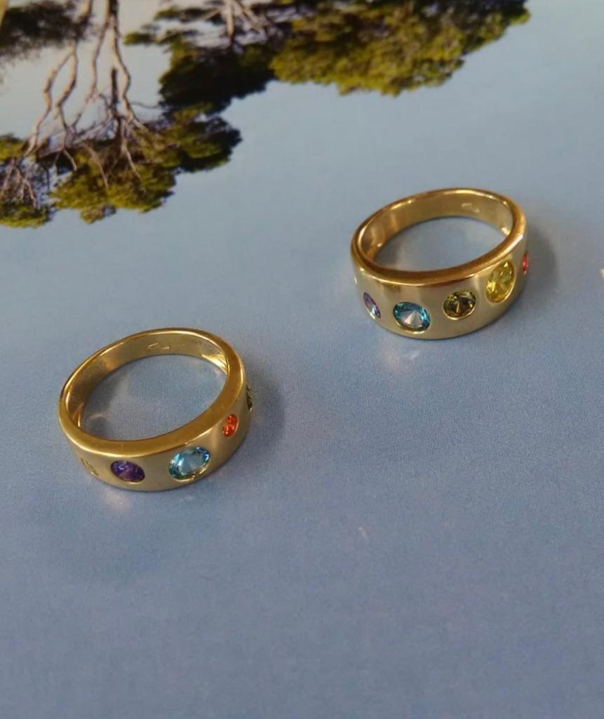Sortijas anchas, una de ocho milímetros y otra de seis, con circonitas de distintos tamaños y colores ( naranja, amarilla, verde, azul y lila).