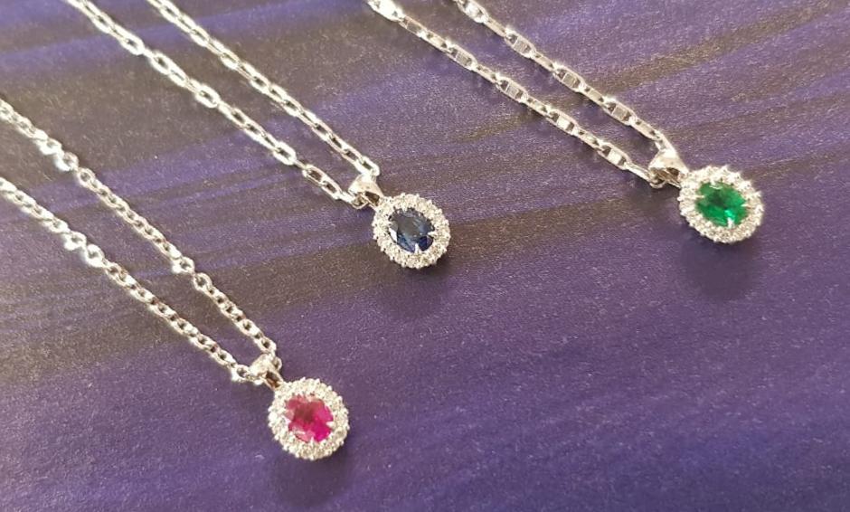 Rosetones de oro blanco con diamantes, uno con rubí, otro con zafiro y otro con esmeralda, la piedra central hace 4x3 milímetros y llevan 16 brillantes alrededor que en total hacen 0,08 quilates.