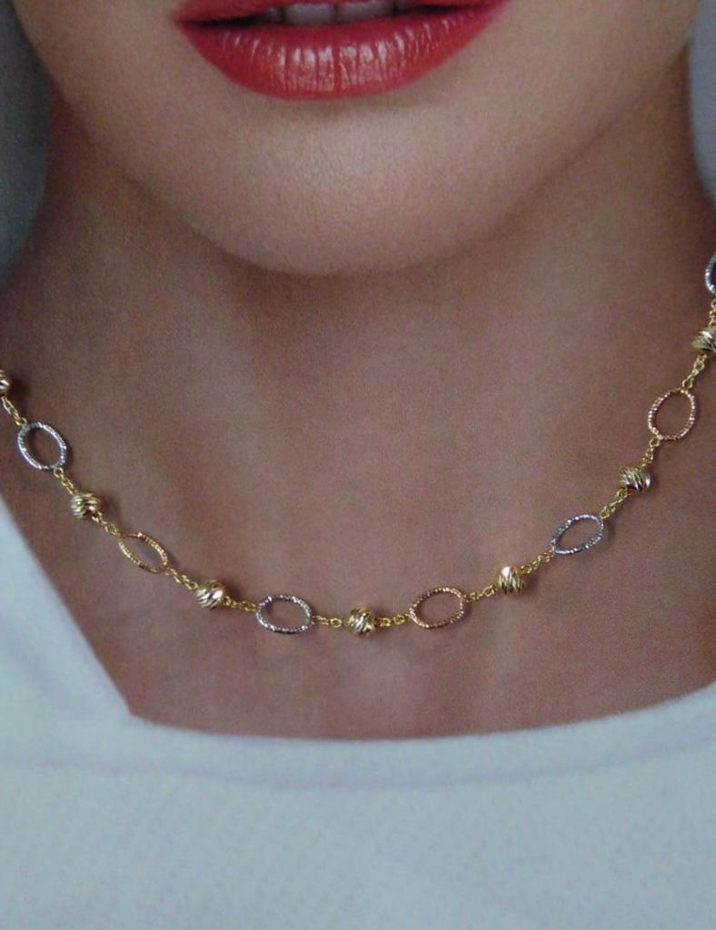 Collar de 42 centímetros de largo, tricolor, con anillas blancas y rosas y bolas lapidadas de oro amarillo.