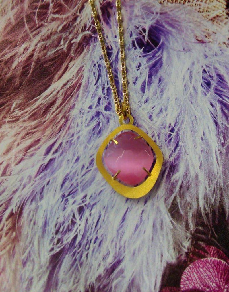 Colgante de oro amarillo mate con una piedra rosa opaca en forma de rombo de 16x18 milímetros engastada por 4 garras.