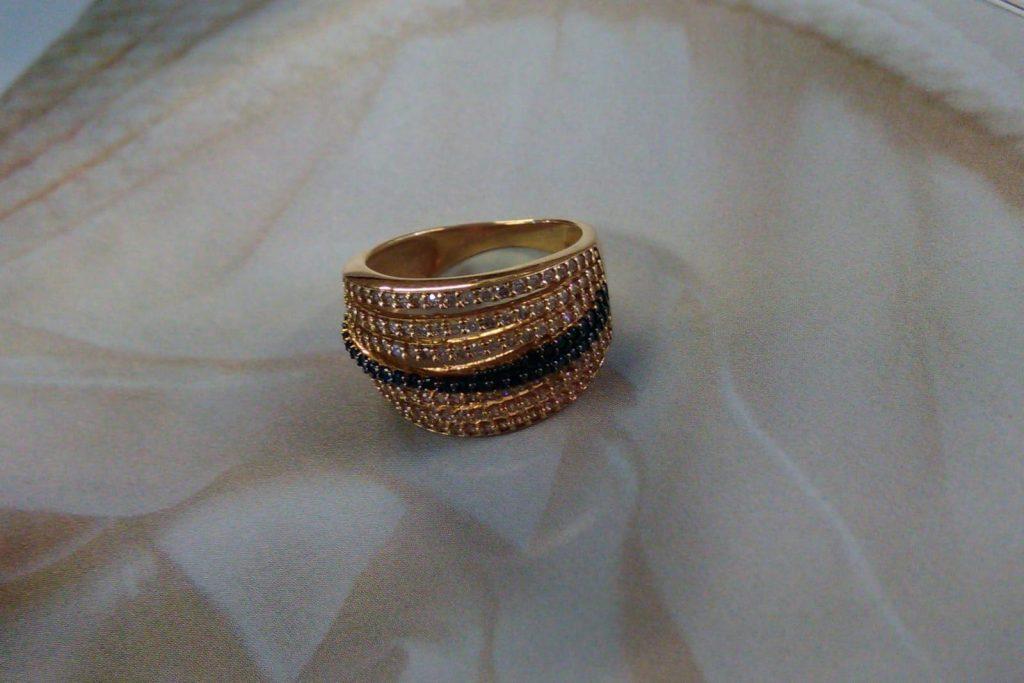 Sortija de oro rosado de 13 milímetros de ancho, con seis tiras de circonitas blancas y dos tiras de circonitas negras cruzadas, montadas en garras.