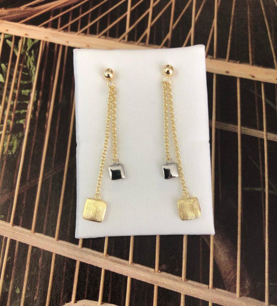 Pendientes bicolor, largos, con una bola de oro amarillo de la que cuelgan dos cadenas con dos cuadrados, uno de oro blanco brillo y el otro de oro amarillo mate, con cierre de presión.