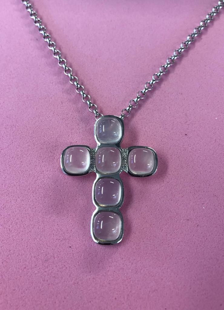 Cruz de oro blanco brillo, de 30x39 milímetros, con seis brillantes y seis piedras de color rosa-grisáceo.