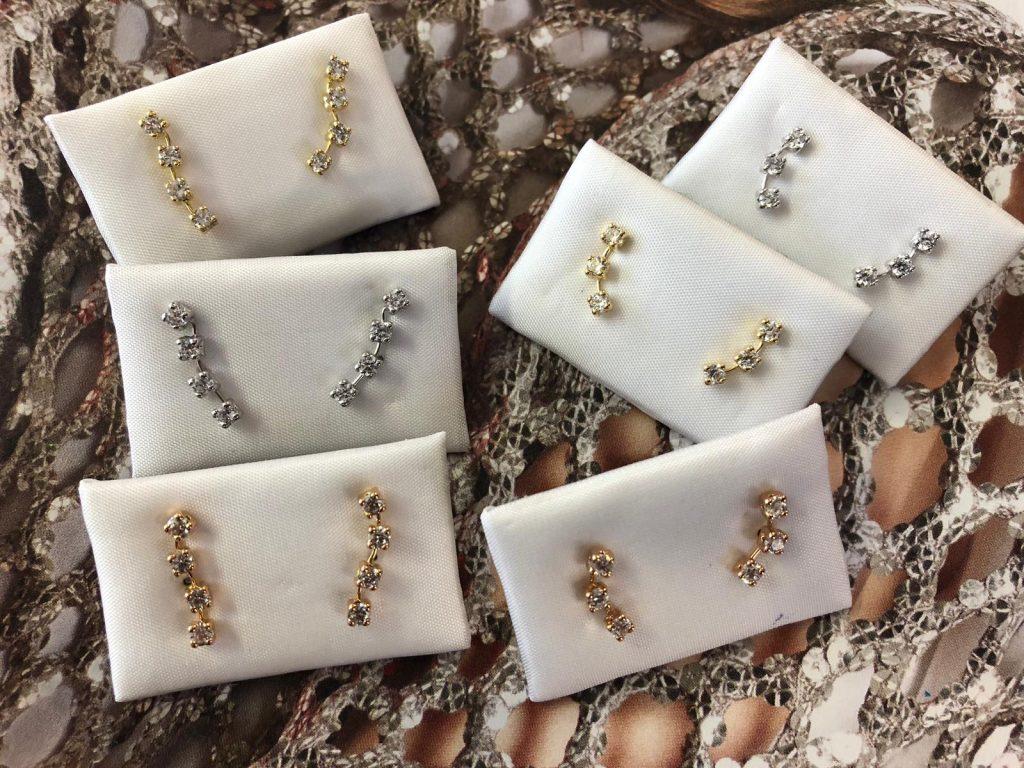 Pendientes trepadores en oro amarillo, blanco y rosa, con circonitas en fila montadas en cuatro garras, unos con cuatro y otros con tres circonitas, con cierre de presión.