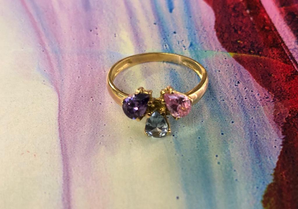 Anillo de oro amarillo con tres piedras perilla en distintos colores: lila, azul y rosa.