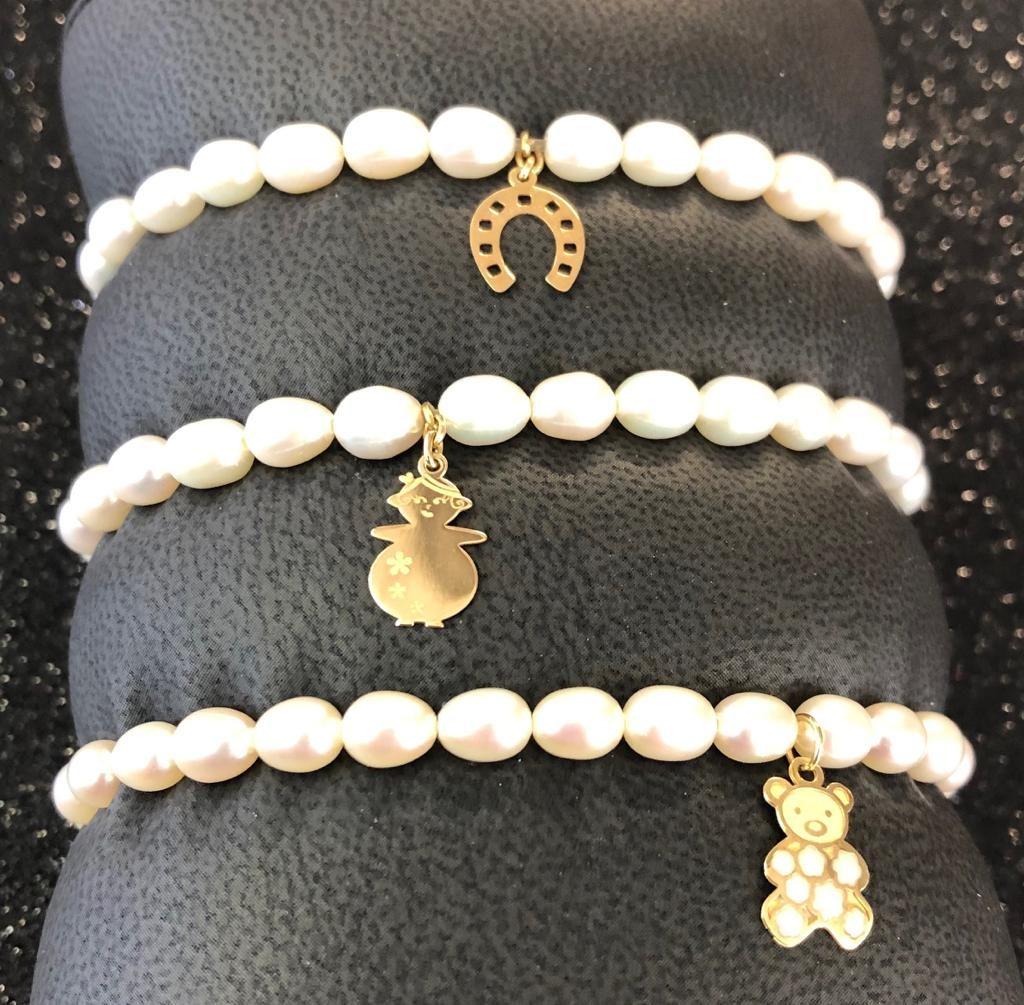 Pulseras elásticas con 22 perlas ovales y motivos colgando en oro amarillo.