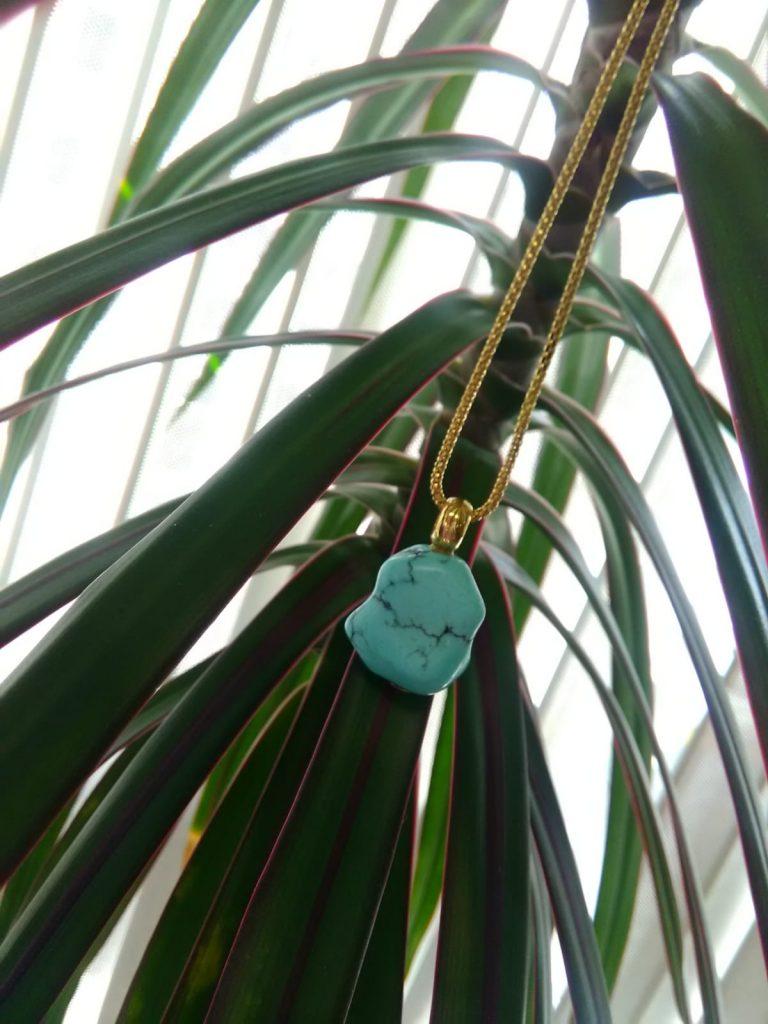 Colgante de turquesa natural de 20 x 17 milímetros con anilla de oro amarillo de 8 milímetros.