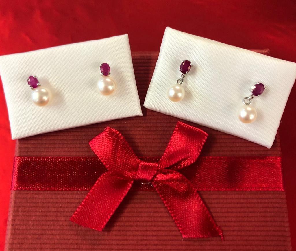 """Pendientes """"tuyyo"""" de oro blanco, con rubí montado en garras y perla, ambos con cierre de presión."""