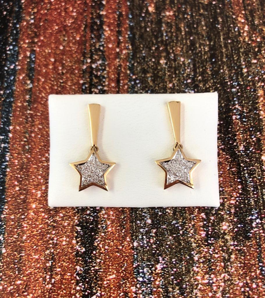 Pendientes semi-largos de oro amarillo con una estrella cuajada de brillantes con grapas en oro blanco y con cierre de presión.