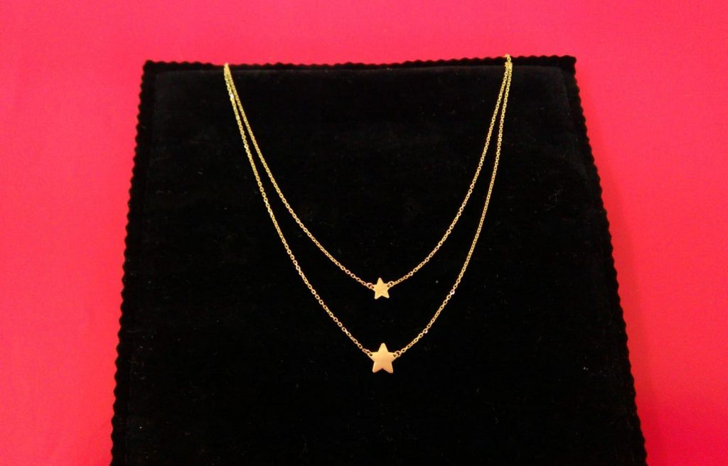 Collar de oro amarillo de 45 centímetros de largo , con anilla a 40 centímetros y cadena doble por delante con dos estrellas de distintos tamaños.