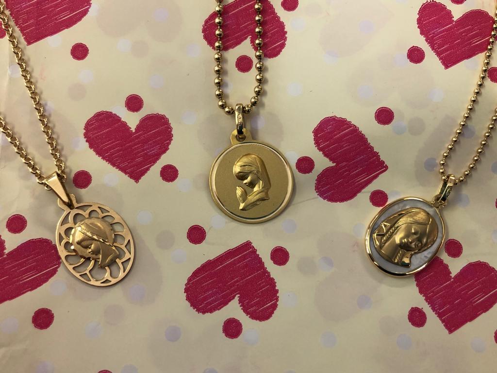 Medallas de oro amarillo, una calada, otra con bisel y una combinada con nácar, con la imagen de la virgen niña, disponibles diferentes modelos y tamaños.
