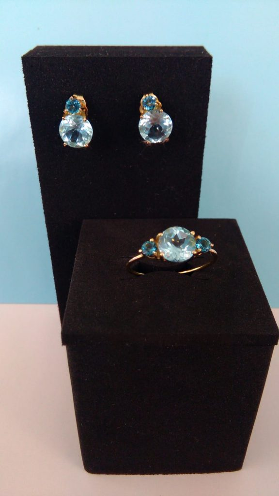 Pendientes de oro amarillo con cierre de presión y piedras de color azul claro y oscuro, anillo de oro amarillo con dos piedras azul oscuro y una azul claro.