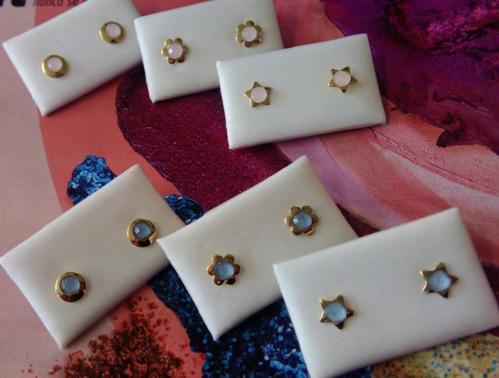 Pendientes de oro amarillo, con diferentes formas ( flor, estrella y circulo) con piedras de color (rosas y azules) talladas y con cierre de presión.