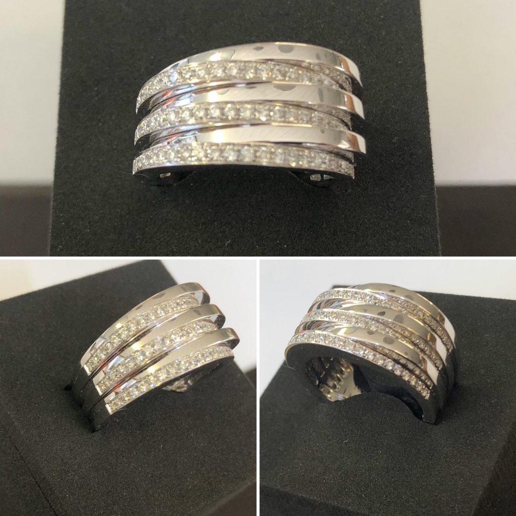 Anillo de oro blanco de 11 milímetros de ancho, compuesto por seis tiras, tres de diamantes y tres de oro blanco, 69 brillantes que hacen un total de 0,57 quilates.