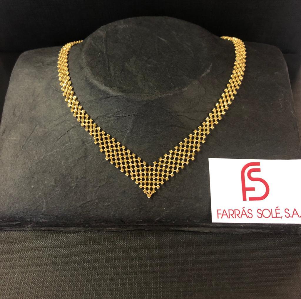"""Collar de oro amarillo, de 42 centímetros de largo, en forma de uve, formado por cadenas """"palline"""" (cadenas de bolas) que tejen una malla."""