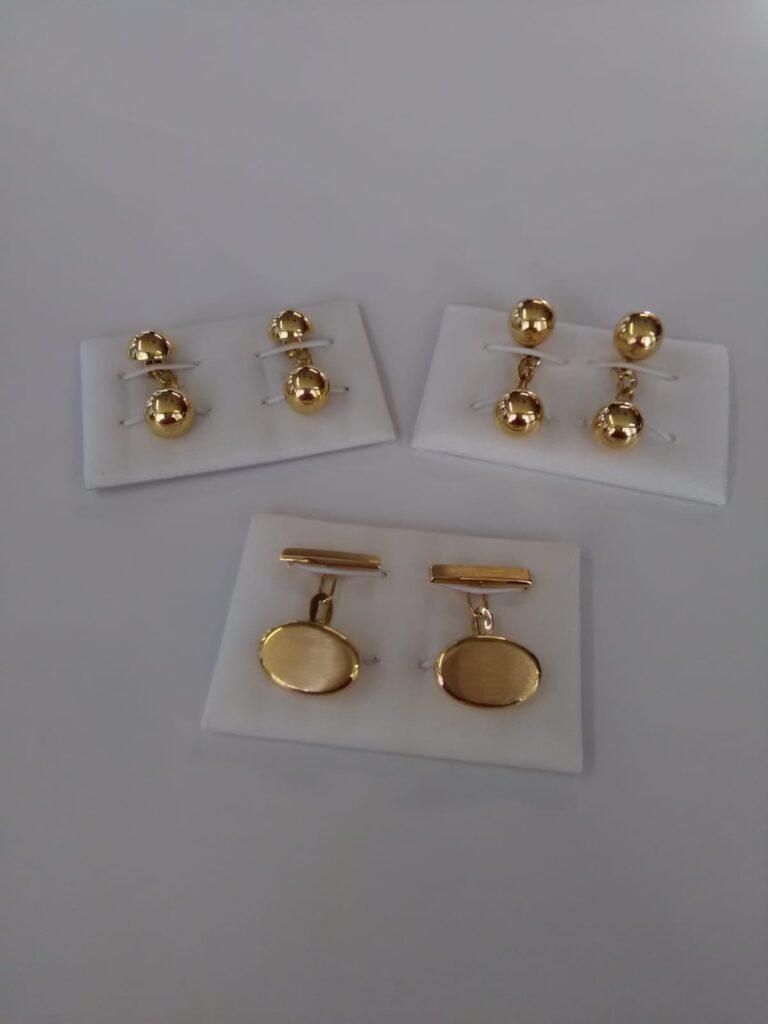 Diferentes modelos de gemelos en oro amarillo, uno con medias bolas, otro de bolas y otro con motivo oval matizado, todos con cadena.